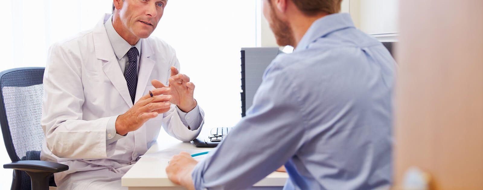 Arzt erklärt Patient die Entstehung einer Analfissur