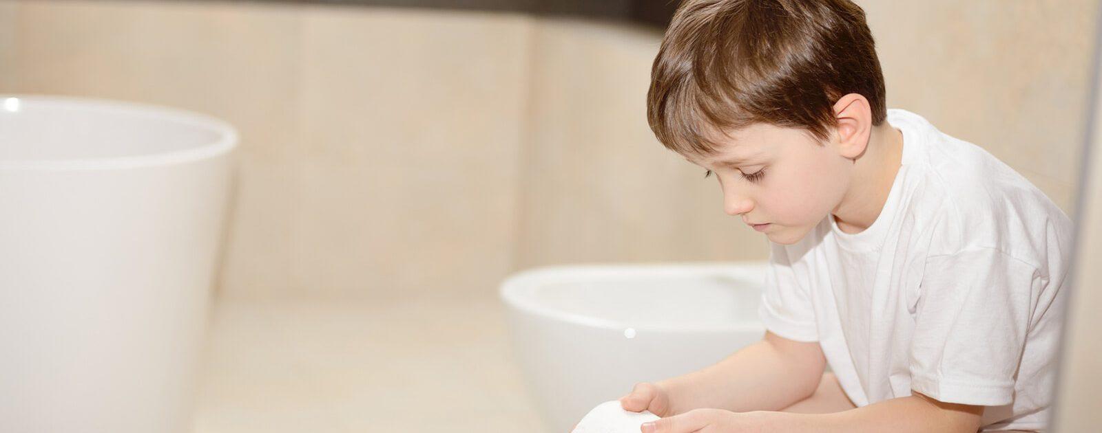 Kind mit Hämorrhoidalleiden auf der Toilette