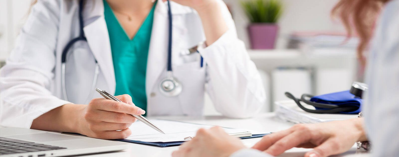 Arzt stellt einer Frau eine Hämorrhoiden-Diagnose