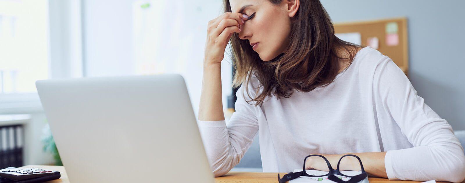 Gestresste Frau vor Laptop leidet an Hämorrhoiden