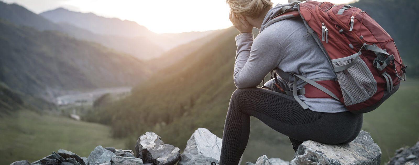 Frau mit Hämorrhoiden sitzt auf kalten Stein in den Bergen