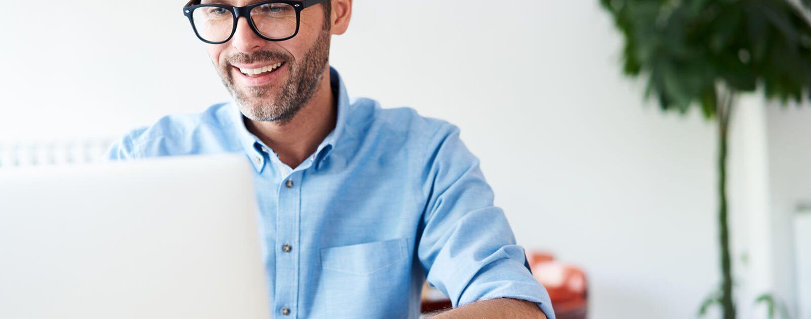 Mann am Laptop macht einen Hämorrhoiden-Selbsttest.