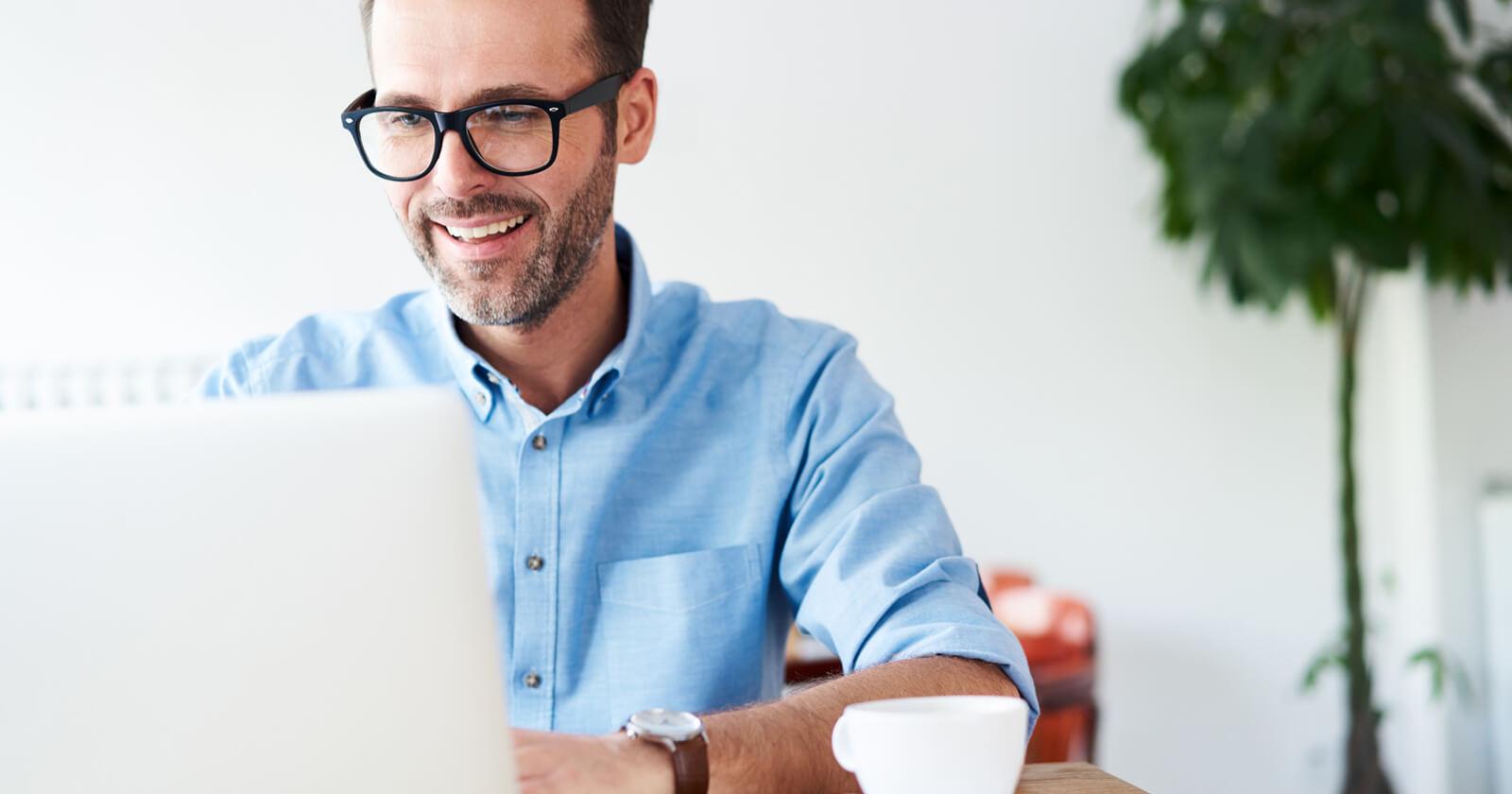 Mann macht am Laptop einen Hämorrhoiden-Selbsttest