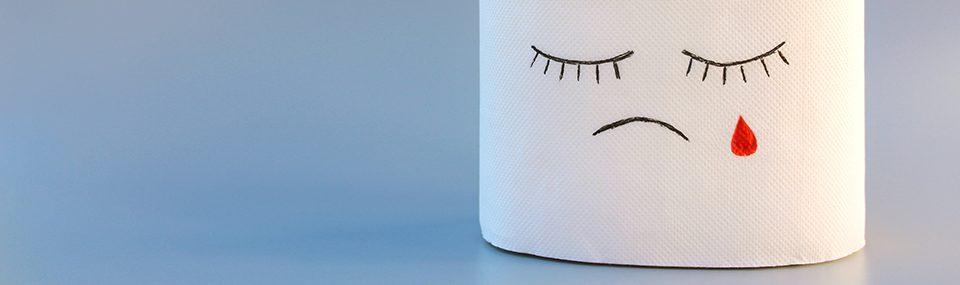 Toilettenrolle mit aufgemaltem, traurigen Gesicht und roter Träne, die auf blutende Hämorrhoiden hindeuten soll.